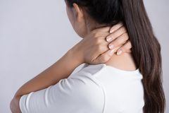 Closeup woman neck and shoulder pain and injury. Health care and medical concept stock photography