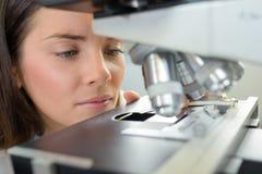 Closeup woman next to microscope Royalty Free Stock Photos