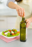 Closeup on woman opening bootle of olive oil to add into salad Stock Photos