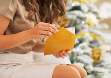 Closeup on woman opening christmas postcard near christmas tree Royalty Free Stock Image