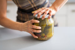 Closeup on woman opening jar of pickled cucumbers Stock Images