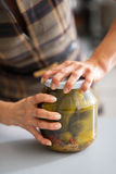 Closeup on woman opening jar of pickled cucumbers Stock Photos