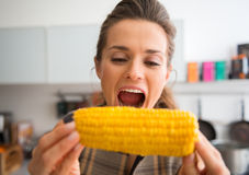 Closeup of woman opening mouth wide to take bite of corncob Stock Image