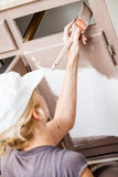 Closeup of Woman Painting Kitchen Cabinets Royalty Free Stock Photos