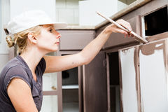 Closeup of Woman Painting Kitchen Cabinets Royalty Free Stock Images