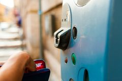 Closeup of woman paying ticket at parking machine outdoor. Woman hand paying parking ticket with wallet Royalty Free Stock Photography