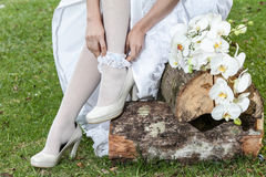 Closeup of woman placing league with shoes and bouquet of flowers Stock Photos