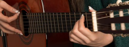 Closeup of woman playing guitar. Closeup of young woman playing acoustic guitar Royalty Free Stock Photo
