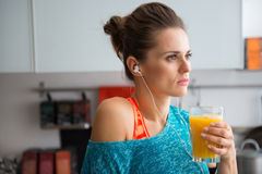 Closeup of woman in profile wearing workout gear holding juice Stock Photo