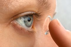 Woman putting contact lens in her eye Stock Image