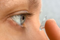 Closeup of woman putting contact lens in her eye Royalty Free Stock Photo
