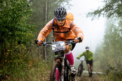Closeup of woman racer cyclist rides through forest royalty free stock photography