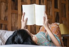 Closeup woman reading a book on bed in her bedroom in the morning stock images