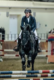 Closeup woman rider horse overcomes obstacles sports complex indoors. Chelyabinsk, Russia - November 22, 2015: closeup woman rider horse overcomes obstacles Stock Images