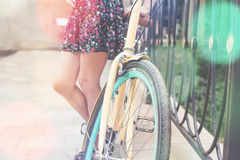 Closeup of woman riding by blue vintage city bicycle Stock Photos