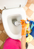 Closeup of woman in rubber gloves cleaning toilet with brush Royalty Free Stock Photos