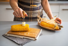 Closeup on woman rubbing boiled corn with butter Royalty Free Stock Images