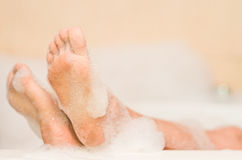 Closeup of woman's feet covered with foam bubbles Royalty Free Stock Photo