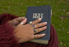 Closeup with a Woman's Hand on a Bible. Closeup of a woman's hand with many rings on a worn black Holy Bible.  Darker skin hand wearing burgundy clothing Royalty Free Stock Photography
