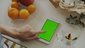 Closeup of woman`s hand browsing smartphone with green screen on kitchen table at home stock video