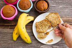 Closeup Woman's hand hold a fork to slice banana cake on white p Stock Photo