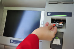 Closeup of woman's hand inserting card into ATM Royalty Free Stock Photography