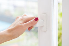 Closeup of woman's hand open a window Royalty Free Stock Image