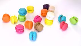 Closeup of a woman's hand picking and aligning colorful macaron (macaroon) dessert food in fancy decoration on white isolated back. Ground on 1920x1080 HD stock video