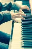 Closeup woman`s hand playing piano Stock Photos