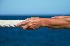 Closeup of woman's hand pulling rope Royalty Free Stock Photography