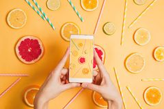 Closeup of woman`s hand with a smartphone making picture of various citrus fruits flatlay arrangement. Selective focus. Food photography or blogging concept stock photography