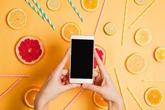 Closeup of woman`s hand with a smartphone making picture of various citrus fruits flatlay arrangement. Smart phone with black copyspace. Selective focus. Food Stock Photography