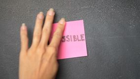 Sticky note on the blackboard. Closeup woman`s hand sticking note with Possible word on the blackboard - video in slow motion stock video footage