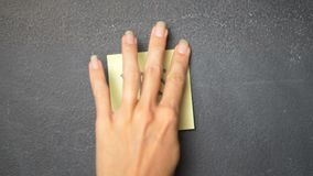Sticky note on the blackboard. Closeup woman`s hand sticking note with Yes word on the blackboard - video in slow motion stock video footage