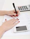 Closeup of woman's hand writing on organizer Stock Photo