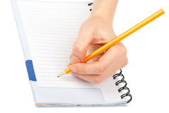 Closeup of woman's hand writing on paper. On isolated white background Royalty Free Stock Photo