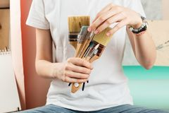 Woman`s hands holding and picking various paint brushes. Closeup of woman`s hands holding and picking various paint brushes, selective shallow focus royalty free stock photo