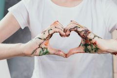 Closeup of woman`s hands painted with watercolors in form of a heart. Selective focus stock images