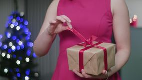 Woman`s Hands Unwrapping a Christmas Gift. Closeup of a woman`s hands unwrapping a Christmas gift or present. A happy wife concept. Soft focus Royalty Free Stock Photos