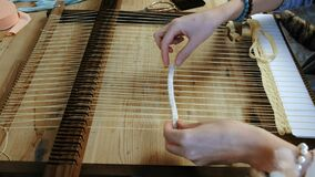 Closeup woman`s hands weaving on a loom frame. Side view. Closeup woman`s hands weaving on a loom frame. Side view stock video footage