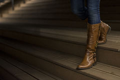 Closeup of woman`s leather boots. On wooden stairs Royalty Free Stock Photography