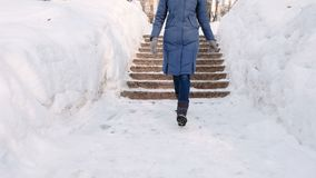 Closeup woman`s legs goes down on a snowy ladder, staircase. Winter park in the city during the day in snowy weather stock footage