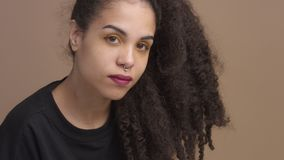 Closeup woman`s portrait. In studio in beige background Curly hair mixed race woman stock video