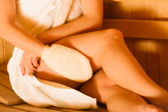 Closeup of woman in sauna with exfoliating glove. Closeup of woman thighs legs in wood finnish spa sauna massaging skin with exfoliating glove. Girl relaxing Stock Photo