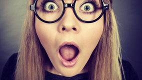Closeup woman shocked face with eyeglasses. Closeup of weirdo woman face wearing big nerd geek eyeglasses having shocked expression Royalty Free Stock Photos