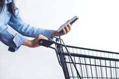 Closeup of woman with shopping cart and shopping list in smartph Stock Image
