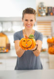 Closeup on woman showing ceramic halloween pumpkin in kitchen Royalty Free Stock Images