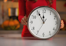 Closeup on woman showing clock in christmas decorated kitchen Stock Photos