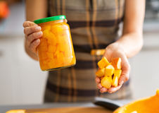 Closeup on woman showing jar of pickled pumpkin Stock Photos