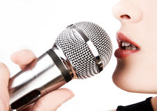 Closeup of woman singing. Close up of woman singing into microphone royalty free stock photography